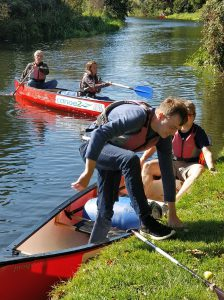 Alex disembarking from the canoe while James S holds it steady